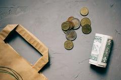 Het geld van contant gelddollars, euro muntstukken met een Kraftpapier-pakket op grijs royalty-vrije stock afbeelding