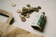 Het geld van contant gelddollars, euro muntstukken met een Kraftpapier-pakket op wit stock foto