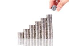 Het geld van de besparing het zetten van muntstuk het groeien in elke kolommen Royalty-vrije Stock Foto's
