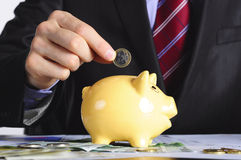 Het geld van de besparing in piggybank Royalty-vrije Stock Foto's