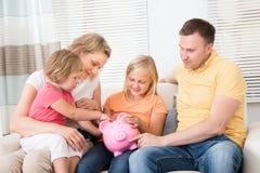 Het geld van de familiebesparing in piggybank Stock Foto's