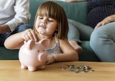 Het geld van de familiebesparing in spaarvarken royalty-vrije stock foto