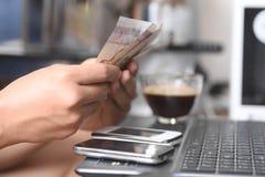 Het geld van de handholding aan het betalen via smartphone stock fotografie
