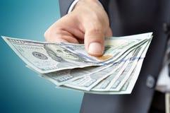 Het geld van de handholding - de dollarrekeningen van Verenigde Staten (USD) Stock Fotografie