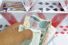 Het geld van de handholding met dek van speelkaarten op de achtergrond Concept het gokken en verslaving Stock Afbeeldingen