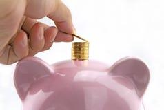 Het geld van de handstorting op de bovenkant van spaarvarken royalty-vrije stock afbeeldingen