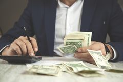 Het geld van de mensenhand met calculator stock afbeeldingen