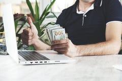 Het geld van de mensenhand met toetsenbord stock foto
