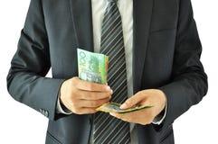 Het geld van de zakenmanholding - Australische dollars stock afbeelding