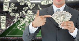 Het geld van de zakenmanholding bij voetbalstadion die corruptie vertegenwoordigen stock afbeelding