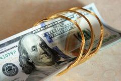 Het geld van dollarrekeningen met goud Stock Foto's