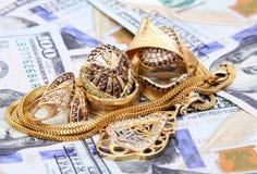 Het geld van dollarrekeningen met goud Stock Fotografie