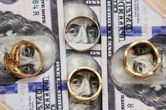 Het geld van dollarrekeningen met goud Stock Foto