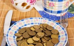 Het geld van het muntstuk op een plaat Stock Afbeelding