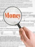 Het Geld van Word, vergrootglas ter beschikking Royalty-vrije Stock Foto