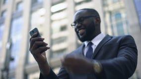 Het geld van zakenmanwinsten in online weddenschappen, die telefoon voor elektronische transactie met behulp van stock video