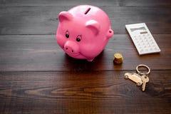 Het geld voor koopt auto Moneybox in vorm van varken dichtbij keychain in vorm van auto, muntstukken, calculator op donkere houte stock foto's