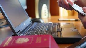 Het geldclose-up van de handentelling op de achtergrond van laptop en paspoort stock videobeelden