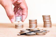 Het geldconcept van de besparing Muntstuk en vage dichte omhooggaande vingergreep stac Royalty-vrije Stock Afbeelding
