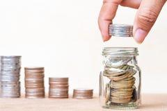 Het geldconcept van de besparing Sluit omhoog de stapelmuntstukken van de vingergreep aan arrang stock fotografie
