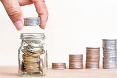 Het geldconcept van de besparing Sluit omhoog de stapelmuntstukken van de vingergreep aan arrang stock foto's