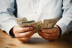 Het geldcontant geld van de mensentelling in zijn hand De economie, besparing, salaris en schenkt concept royalty-vrije stock foto's
