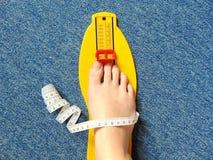 Het gele apparaat van de voetmeting met naakte voet op met het meten van band Stock Afbeelding