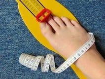 Het gele apparaat van de voetmeting met naakte voet op met het meten van band Royalty-vrije Stock Fotografie