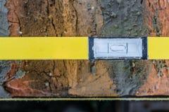 Het gele bellenniveau ligt op de muur van het baksteenmetselwerk met het rijgen van koord Gecentreerde bel stock foto's
