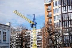 Het gele blauw van de bouwkraan dichtbij het gebouw stock fotografie
