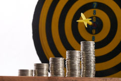 Het gele pijltje raakte in het centrum van een doel met stapel muntstukken Stock Afbeeldingen