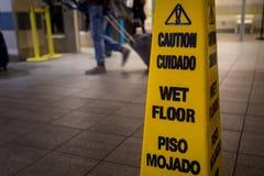 Het gele teken van de voorzichtigheids gladde natte vloer stock afbeelding