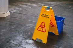 Het gele teken van de Voorzichtigheids natte vloer op natte vloer met blauwe emmer Stock Foto