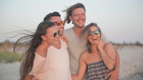 Het gelijk maken bij het strand Portret van Vier Vrienden die Pret samen bij de Kust tijdens Windy Weather en Genieten van hebben stock footage