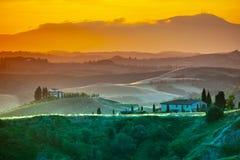 Het gelijk maken in Toscanië Hilly Tuscan-landschap in gouden stemming in zonsondergangtijd met silhouetten van cipressen en land Royalty-vrije Stock Afbeeldingen