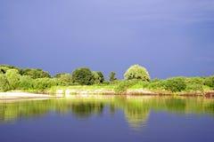 Het gelijk maken van helder zonlicht over de rivier Pripyat Regenwolken juli De zomer Witrussisch landschap stock fotografie