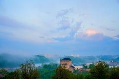 Het gelijk maken van oude stad in de mist Grote steentoren Schemering in kamenetz-Podolsk Lage wolken stock fotografie