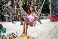 Het gelooide jonge meisje heeft een rust zitting in de hangmat en het kijken aan de kant op de achtergrond van het kustkamp royalty-vrije stock foto's
