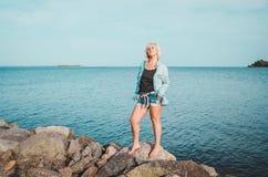 Het gelooide vrouw stellen bij het strand op de zomerdag, die omhoog eruit zien Dromerig wijfje in jeanskleren, bevindende rotsac Stock Afbeelding