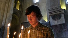 Het geloven van de mens zet een kaars en bidt vóór een pictogram in de Orthodoxe Katholieke Kerk stock video