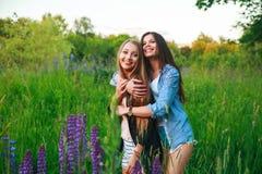Het Geluk Communautair Concept van de meisjesvriendschap Twee glimlachende vrienden die in openlucht koesteren Royalty-vrije Stock Afbeelding