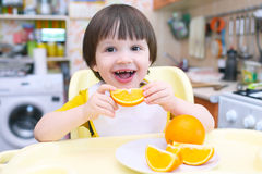 Het gelukkig eet glimlachen van 2 jaar kindsinaasappel Stock Fotografie
