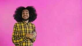 Het gelukkige aantrekkelijke jonge Afro-Amerikaanse mens gebruiken telefoneren en het krijgen van goed nieuws op purpere achtergr stock video