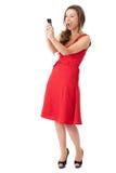 Het gelukkige aantrekkelijke wijfje in rode kleding neemt foto's Royalty-vrije Stock Fotografie