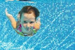 Het gelukkige actieve onderwaterkind zwemt en duikt in pool stock foto