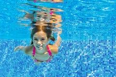 Het gelukkige actieve onderwaterkind zwemt en duikt in pool stock afbeelding