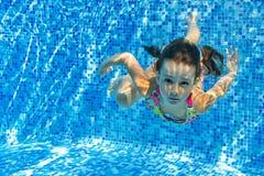 Het gelukkige actieve onderwaterkind zwemt en duikt in pool royalty-vrije stock foto's