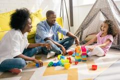 het gelukkige Afrikaanse Amerikaanse familie spelen met kleurrijke blokken samen op vloer royalty-vrije stock foto's