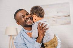 het gelukkige Afrikaanse Amerikaanse grootvader aanbiddelijk koesteren weinig kleinkind stock afbeelding