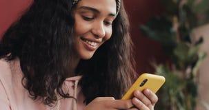 Het gelukkige Afrikaanse Amerikaanse meisjes thuis babbelen en tekstberichten op smartphonezitting op het bed De jonge vrouw ontv stock footage